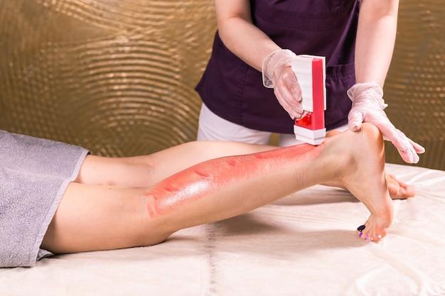 Encerando a perna da mulher. procedimento de depilação para esteticista em cera de salão. encerar o corpo feminino para depilação por