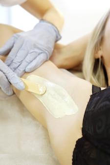 Encerar a axila da mulher com uma espátula. procedimento de depilação de esteticista de cera de salão