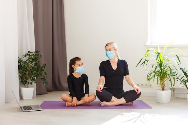 Encerramento do covid-19. mãe e filha em quarentena, fazendo ioga dentro de casa. mãe e filha fazendo meditação durante o bloqueio. saúde, exercícios em casa e autocuidado para isolamento de coronavírus.