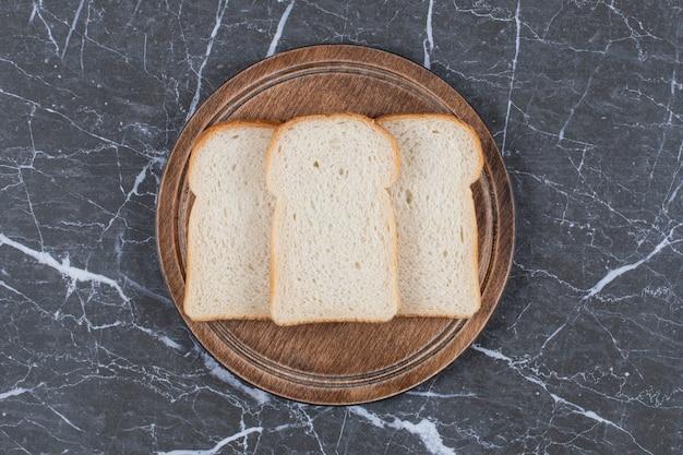 Encha a foto de pão fatiado na tábua de madeira.