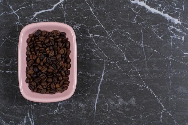 Encha a foto de sementes de café marrom em uma tigela rosa.