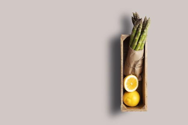 Encha a vista de limão e espargos isolados em fundo de madeira. adequado para o seu projeto de design.