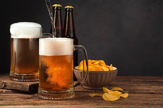 Enchendo canecas de cerveja com cerveja no fundo de batatas fritas e garrafas oktoberfest