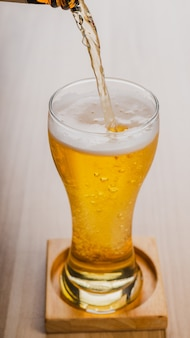 Enchendo copos de cerveja light, cerveja gelada artesanal em um copo na mesa de madeira