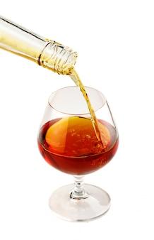 Enchendo um copo de conhaque isolado