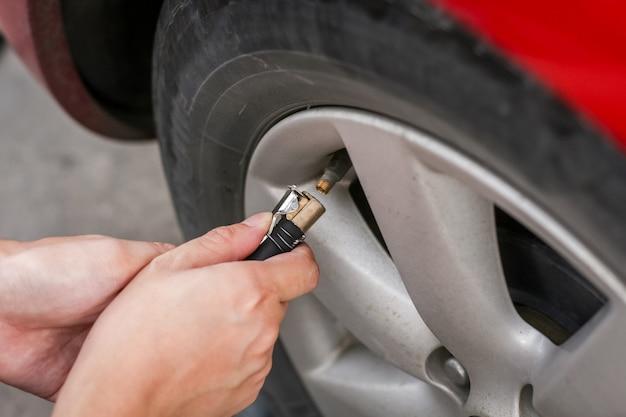 Encher ar em um pneu de carro sujo para aumentar a pressão