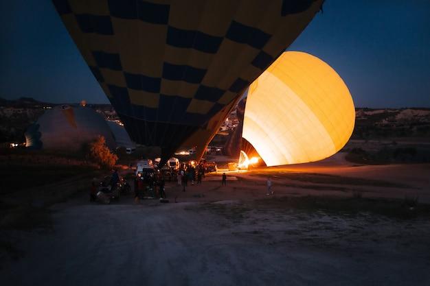 Encher balões de ar quente à noite