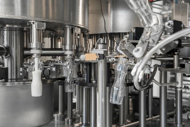 Encher garrafas de plástico com leite na fábrica. equipamento na fábrica de laticínios