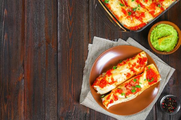 Enchiladas caseiros da galinha no prato na tabela de madeira. vista do topo.
