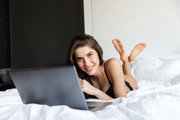 Encontra-se na cama a imagem de uma linda mulher morena usando lingerie, usando o computador portátil.