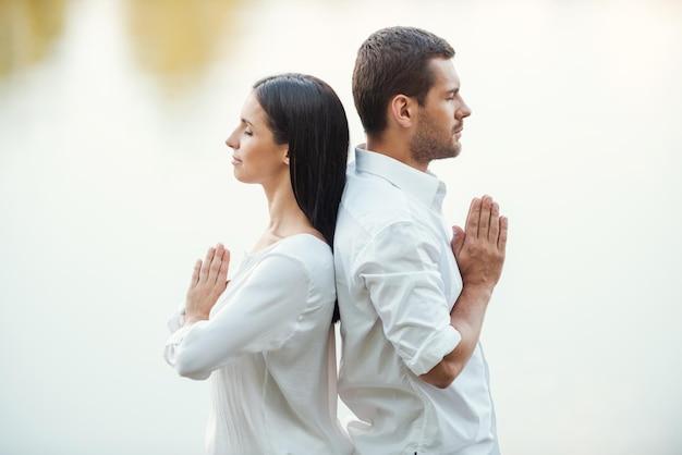 Encontrando harmonia dentro de si. vista lateral de um lindo casal jovem em roupas brancas meditando ao ar livre juntos, em pé de costas um para o outro