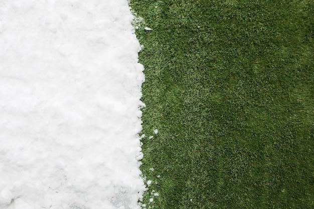 Encontrando neve branca e grama verde close-up. entre o fundo do conceito de inverno e primavera.