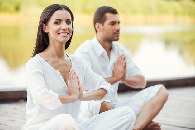 Encontrando paz e harmonia dentro de si. lindo casal jovem com roupas brancas meditando juntos ao ar livre e de olhos fechados