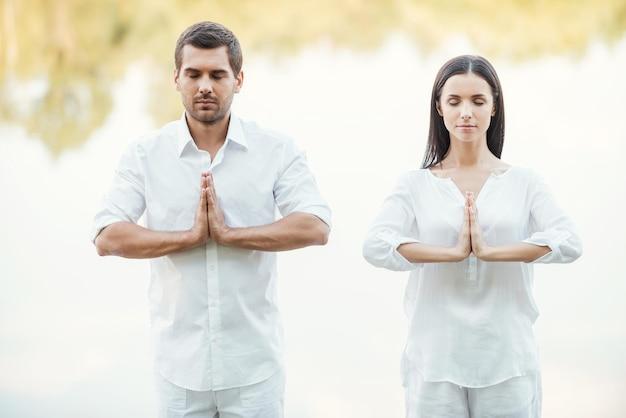 Encontrando tranquilidade. lindo casal jovem com roupas brancas meditando juntos ao ar livre e de olhos fechados