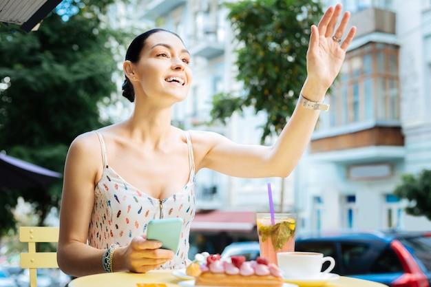 Encontrando um amigo. mulher alegre e emocional sentada à mesa no terraço de um café e sorrindo enquanto acenava para um amigo