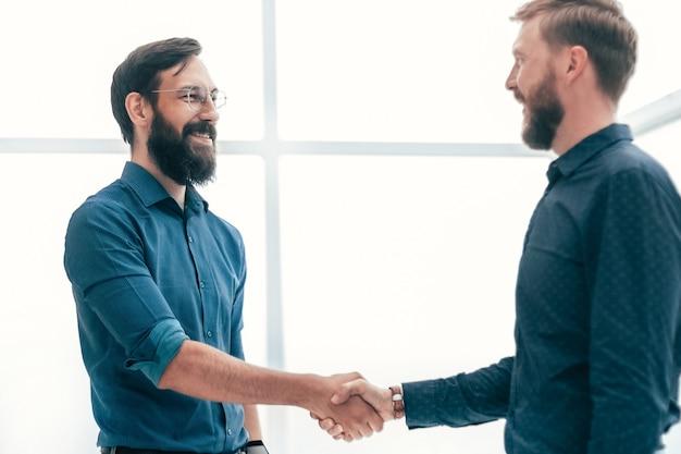 Encontrar e apertar a mão de empresários em um escritório bem iluminado