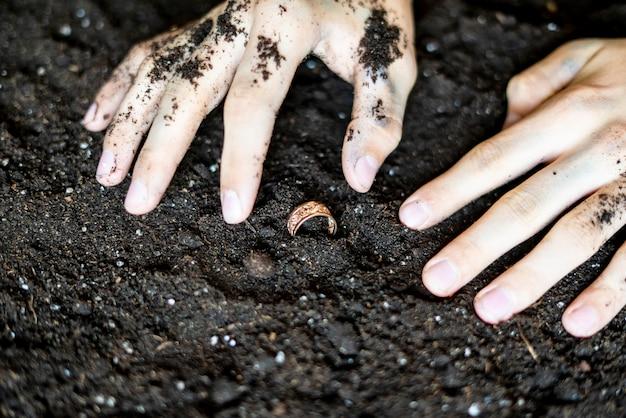 Encontrar um anel de ouro precioso no chão do solo