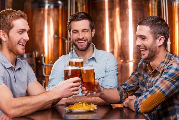Encontrar velhos amigos no bar. três jovens felizes em trajes casuais brindando com cerveja e sorrindo sentados juntos em um bar de cerveja
