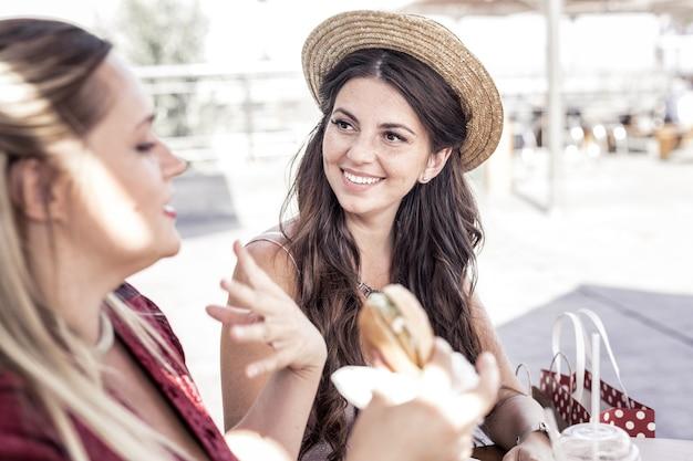 Encontro de amigos. mulher feliz e alegre olhando para a amiga enquanto está sentado com ela à mesa do café