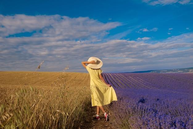 Encontro de dois mundos: uma garota em um vestido amarelo entre um campo de trigo e lavanda