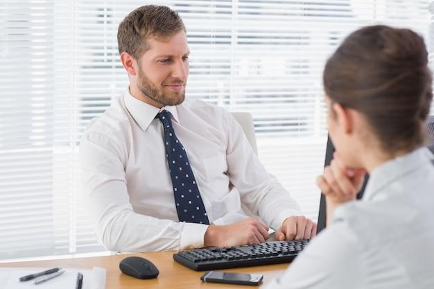 Encontro de empresário com um colaborador em sua mesa