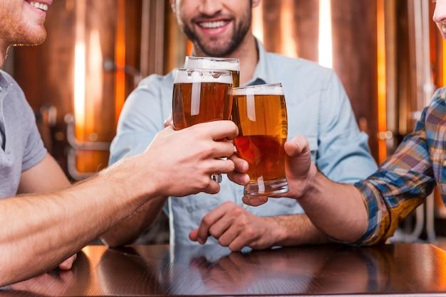 Encontro de velhos amigos. close de três jovens felizes em trajes casuais brindando com cerveja enquanto estão sentados juntos em um bar de cerveja