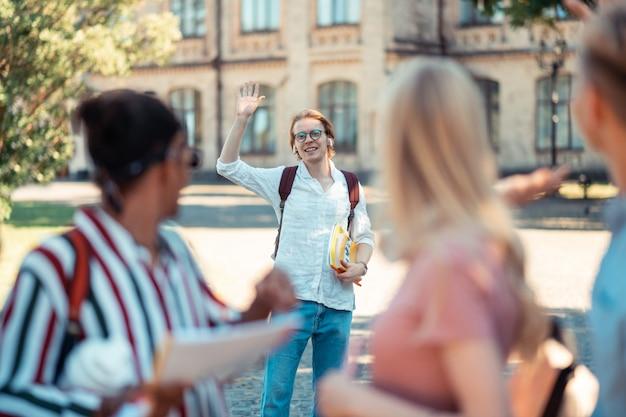 Encontro lá fora. menino sorridente, segurando seus livros com uma mão, acenando com a outra para seus colegas de grupo no pátio da universidade.