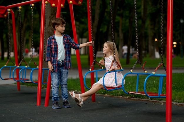 Encontro romântico de crianças, menino e menina em balanços