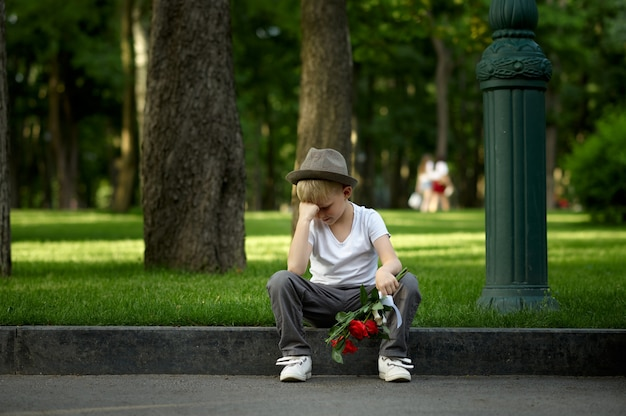 Encontro romântico de crianças no parque de verão, amizade, primeiro amor malsucedido. menino triste com buquê, menina não veio para um encontro. crianças ao ar livre, infância feliz