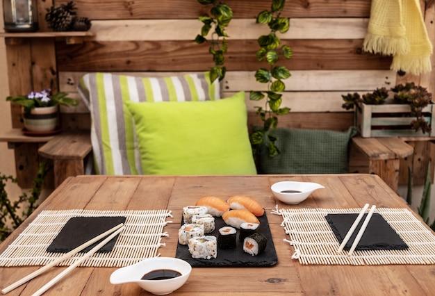 Encontro romântico para duas pessoas num jantar de sushi. mesa de madeira ao ar livre no terraço.