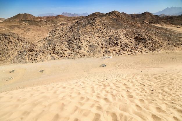 Encosta com pedras no deserto seco. egito quente areia sem vida e montanha rochosa e céu azul em dia ensolarado de verão.
