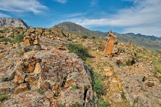Encosta íngreme de montanha rochosa com arbustos e vista da cordilheira