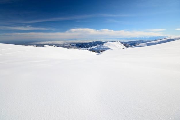 Encosta nevada com excelente vista panorâmica do inverno nos alpes