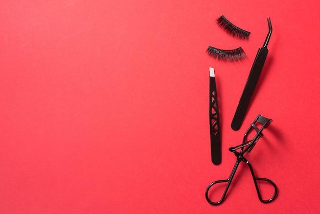 Encrespador preto, cílios postiços e pinças sobre fundo vermelho, copie o espaço