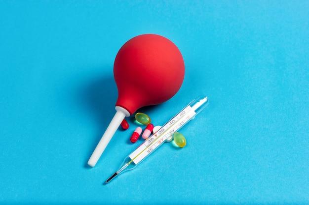 Enema médico de pêra para procedimentos termômetro de mercúrio e pílulas em um fundo azul intoxicação alimentar