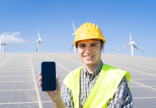 Energia alternativa - engenheiro em planta de painéis solares mostrando tela de telefone, sorriso feliz, energia verde e conceito de indústria ecologicamente correta