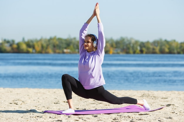 Energia. jovem atleta, mulher treinando, praticando ao ar livre sob o sol de outono