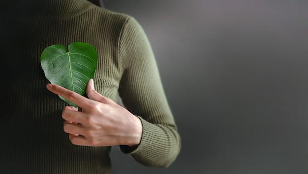 Energia verde, recursos renováveis e sustentáveis. conceito de cuidados ambientais e ecológicos. close-up da mão segurando uma folha verde em forma de coração no peito