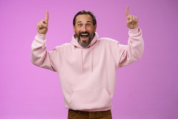 Energizado feliz bonito na moda pai maduro com barba cabelos grisalhos em um capuz rosa elegante vestindo roupa de filho apontando para cima os dedos indicadores, emocionado com o grupo de música favorito na cidade, em pé de fundo roxo.