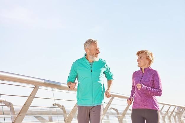 Energize sua vida, casal de família maduro e ativo em roupas esportivas, sorrindo um para o outro enquanto correm