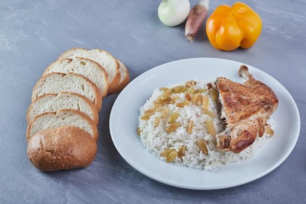 Enfeite de arroz com sultana e frango frito em um prato branco com pão.