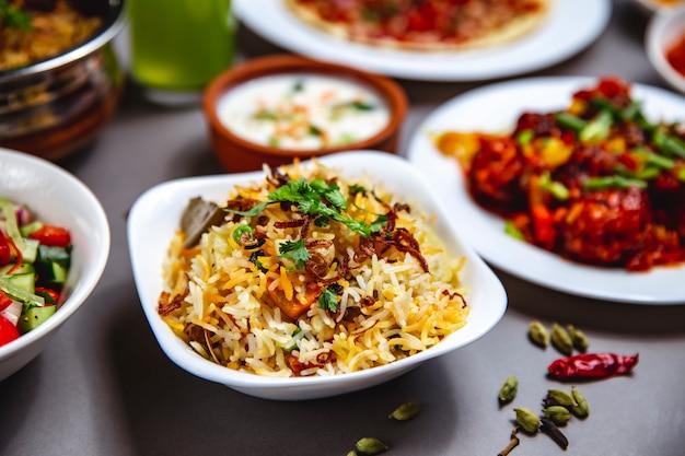Enfeite de arroz de vista lateral com cebola frita cenoura verdes e pimenta em cima da mesa