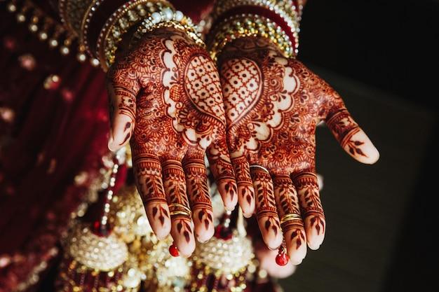 Enfeite de casamento mehndi nas mãos desenhadas por henna