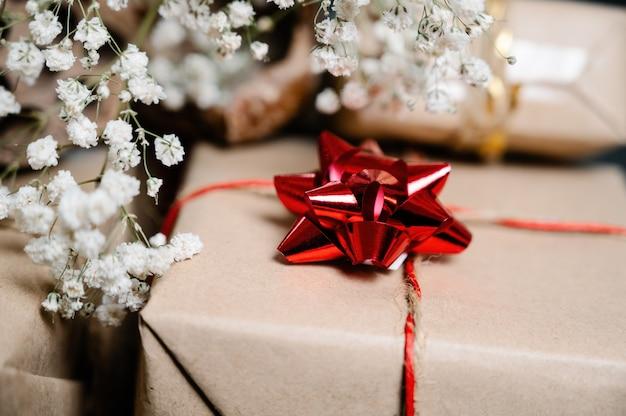 Enfeite de flor vermelha no presente de natal com flores brancas