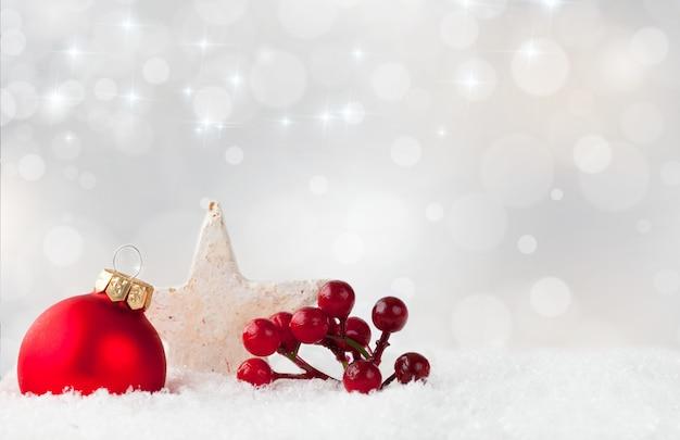 Enfeite de natal vermelho e bagas de arbusto de azevinho e uma estrela branca em uma superfície de neve