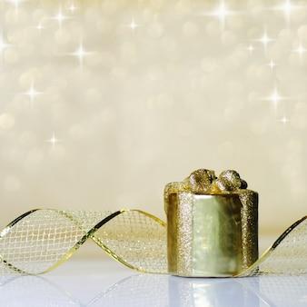 Enfeite de ouro fita de natal em fundo de luzes douradas desfocadas. dof raso.
