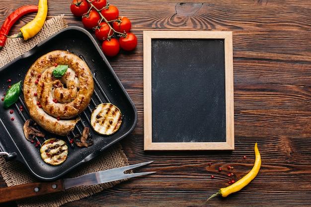 Enfeite deliciosas salsichas grelhadas em espiral perto de ardósia de madeira em branco na mesa
