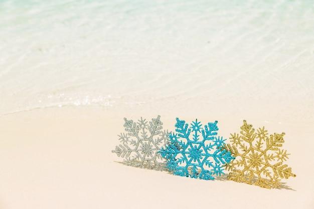 Enfeites de árvore de natal na areia da praia do mar