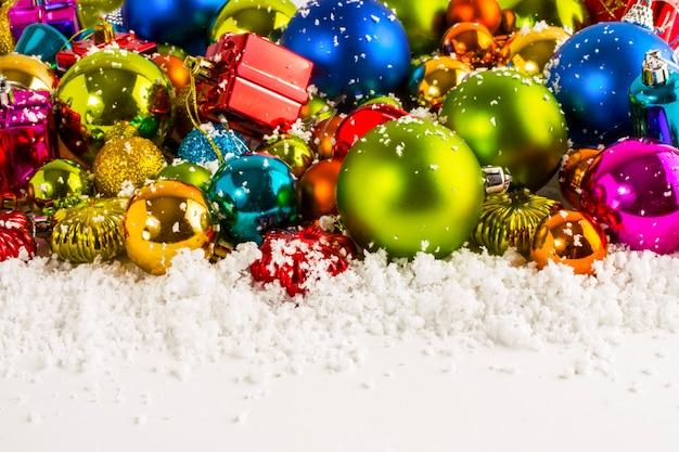 Enfeites de natal azuis, vermelhos, amarelos, verdes, roxos, balões, sinos, caixas de presente, estrelas e neve