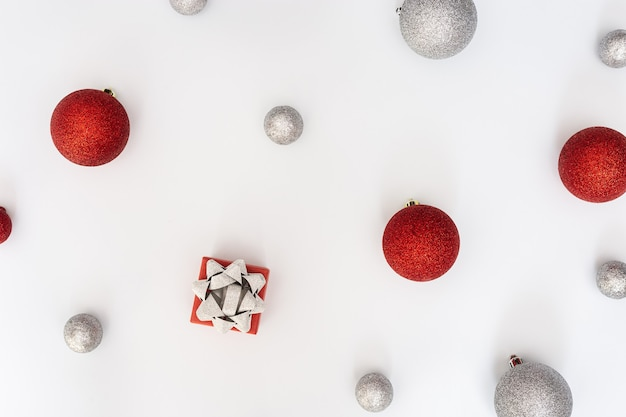 Enfeites de natal bolas vermelhas e prateadas e caixa de presente no feriado de ano novo branco